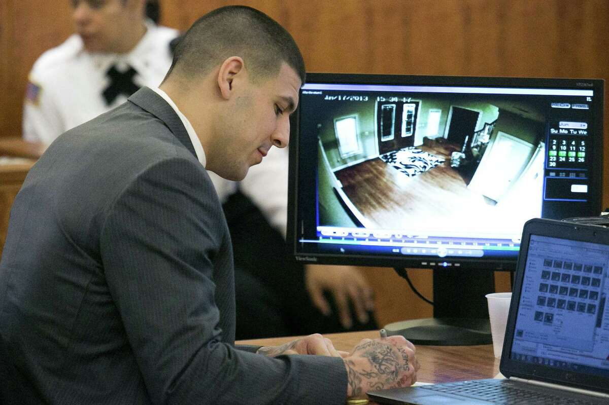 Aaron Hernandez takes notes as surveillance footage is seen during a motion regarding jail phone recordings during his murder trial Wednesday at the Bristol County Superior Court in Fall River, Mass.