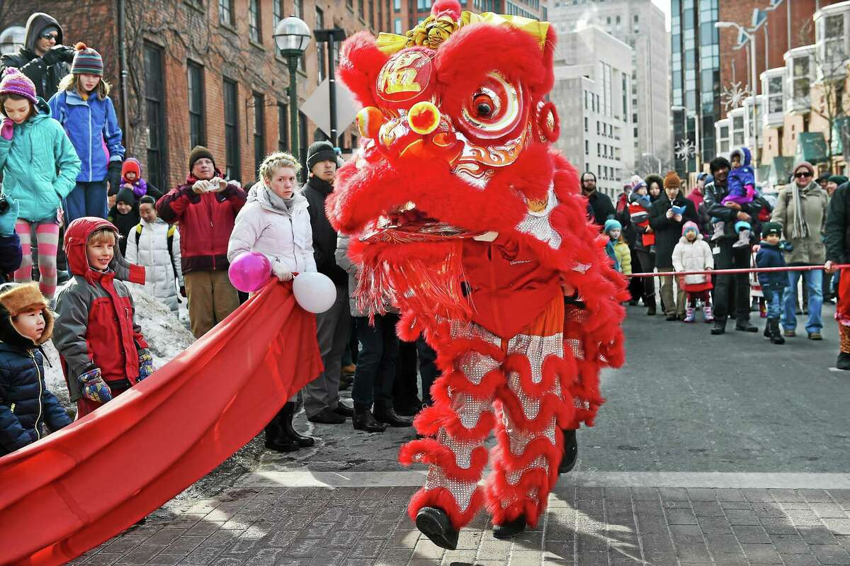The colorful lion dance makes its way down Whitney Avenue in New Haven Saturday morning.