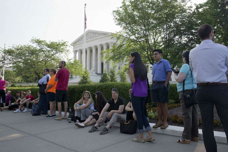 People wait in line to enter the Supreme Court in Washington, Thursday June 25, 2015. The court is expected to hand down decisions today. Two major opinions, health care and gay marriage, are among the remaining to be released before the term ends at the end of June. Photo: AP Photo/Jacquelyn Martin   / AP
