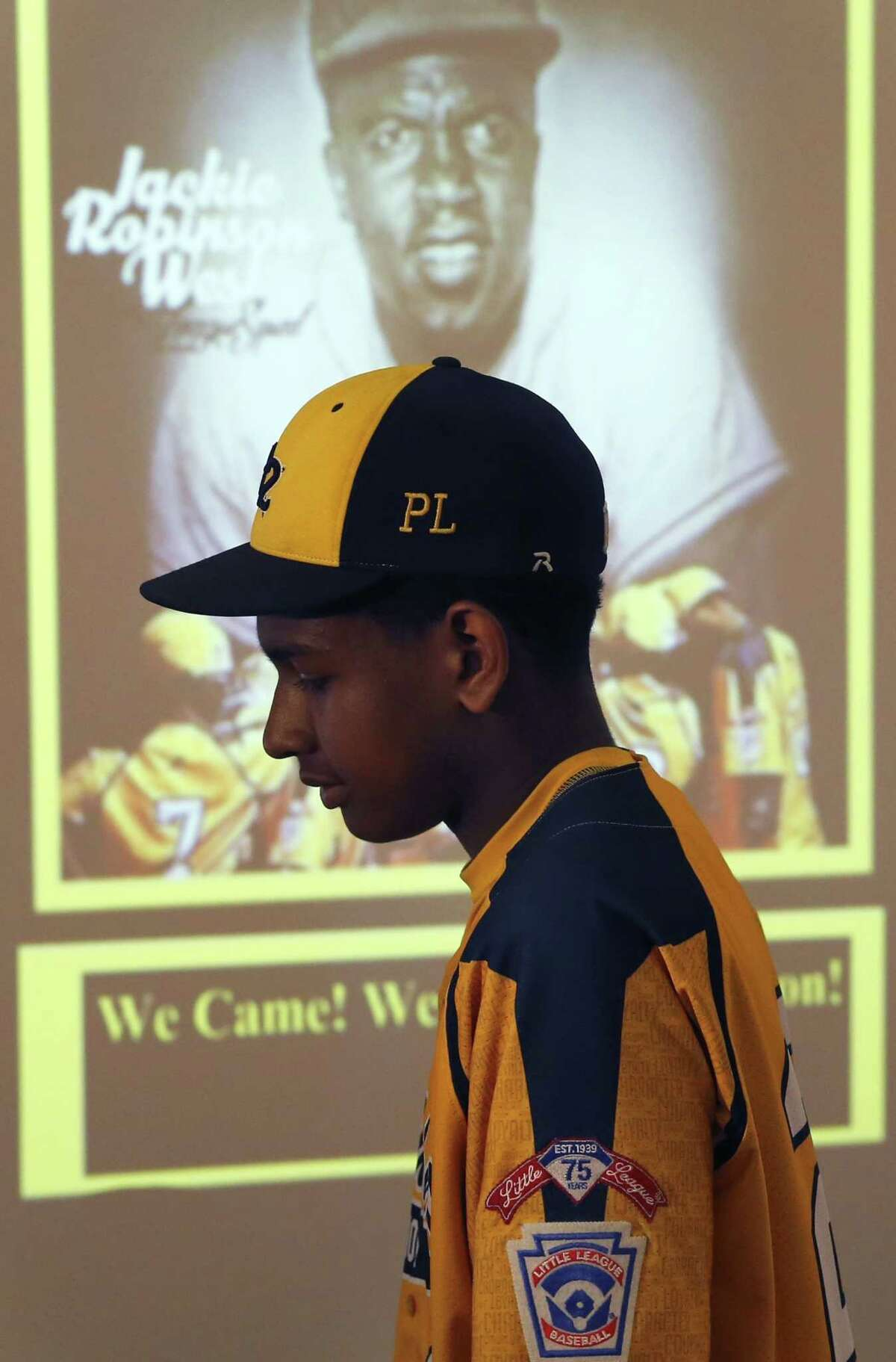 Jackie Robinson West Little League player Prentiss Luster walks past a projected image of Jackie Robinson after team attorney Victor Henderson addressed reporters at a news conference Wednesday in Chicago.