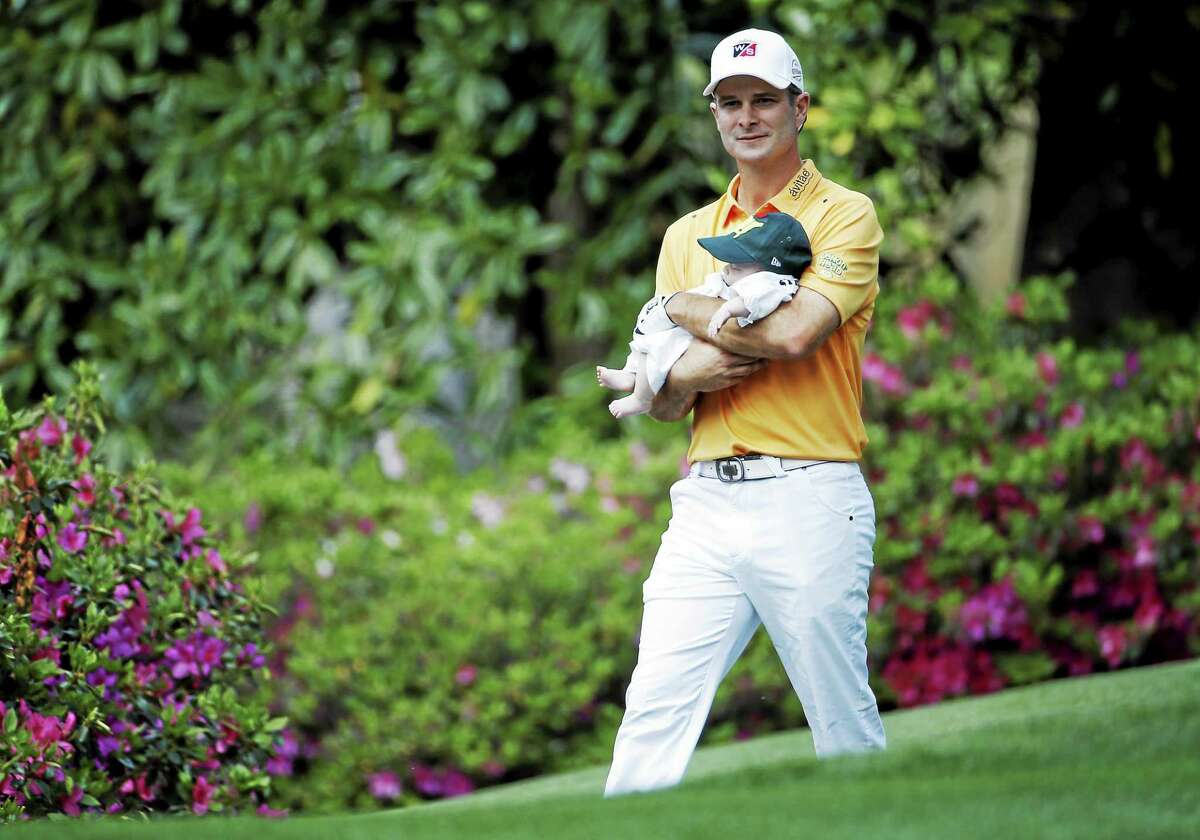 Kevin Streelman carries his daughter, Sophia, down the fifth fairway during the 2014 Masters Par 3 Contest in Augusta, Ga.