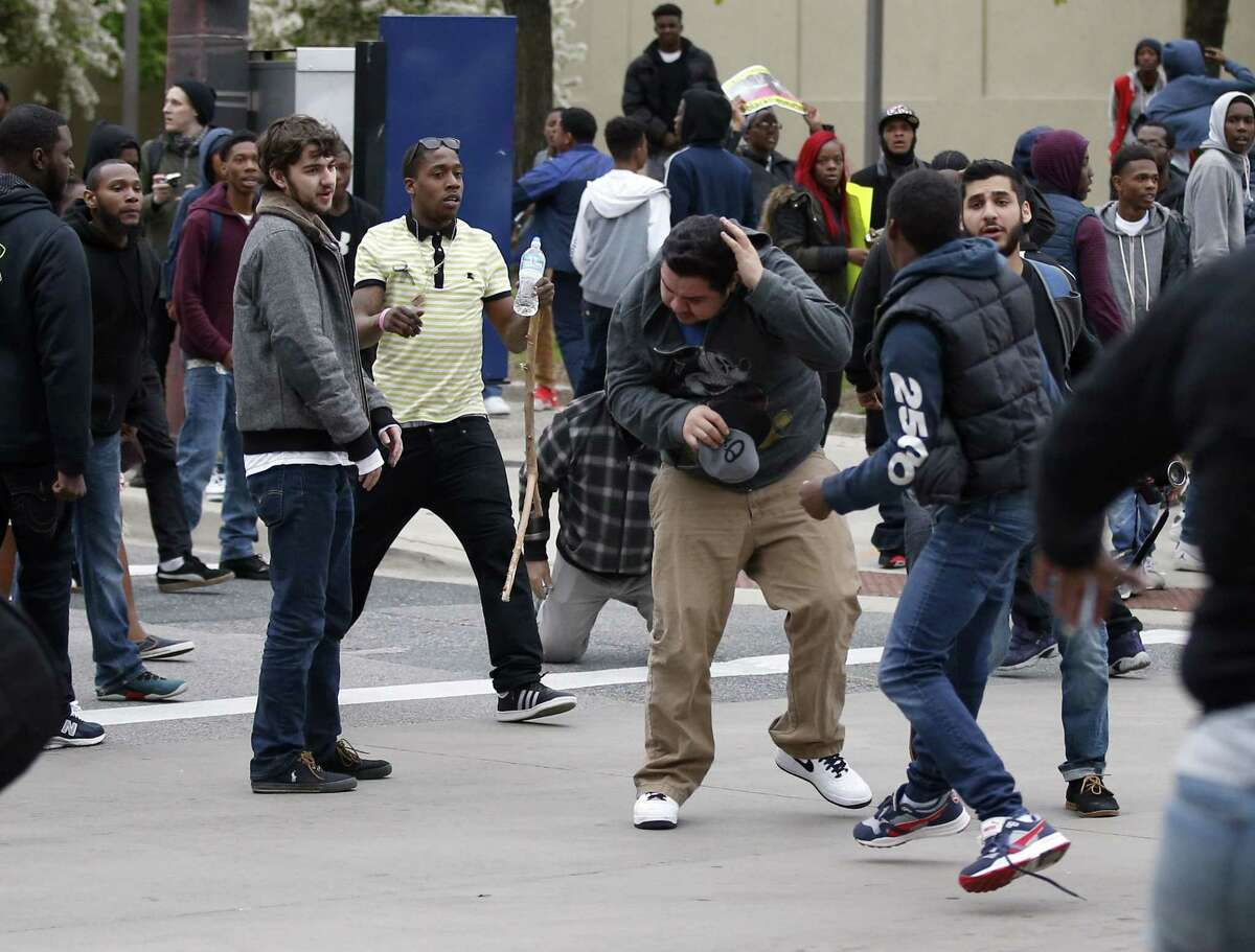 A man, center, shields himself after being struck after a march to City Hall for Freddie Gray, Saturday, April 25, 2015 in Baltimore. Gray died from spinal injuries about a week after he was arrested and transported in a police van.