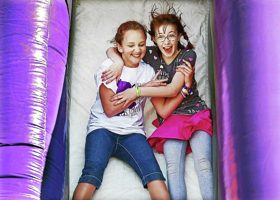 """Natalie Raynor, 10, at left, and her new friend, Annabelle, Farrell, 11, make their way down an inflatable purple slide, arm in arm, meeting for the first time at """"Peace Love & Music from Maren,"""" Saturday afternoon, April 25, 2015, at Jonathan Law High School. The Milford community came together to remember and celebrate the life of stabbing victim Maren Sanchez in a way she would have loved; a festival of art, music, and creative activities. Farrell said, """"I didn't know Maren, but I'm here to show support, celebrate Maren...I'm happy that she is remembered."""" """"I'm here to celebrate her life,"""" added Raynor. Photo: Catherine Avalone - New Haven Register   / New Haven RegisterThe Middletown Press"""