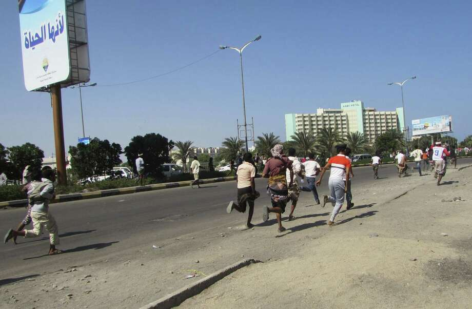 People flee after a gunfire on a street in the southern port city of Aden, Yemen, Wednesday, March 25, 2015. Yemeni President Abed Rabbo Mansour Hadi fled the country by sea Wednesday on a boat from Aden, as Shiite rebels and their allies advanced on the city where he had taken refuge. Aden was tense Wednesday, with schools, government offices, shops and restaurants largely closed.  (AP Photo/Yassir Hassan) Photo: AP / AP