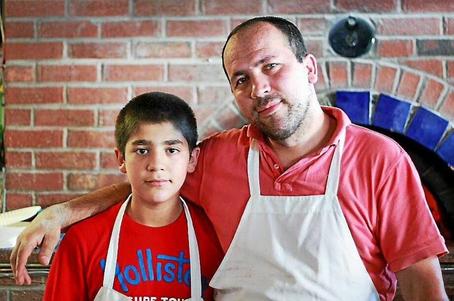 Hacibey Catalbasoglu and his father, Kadir, in younger days at Pizza at the Brick Oven. Photo: Contributed Photo