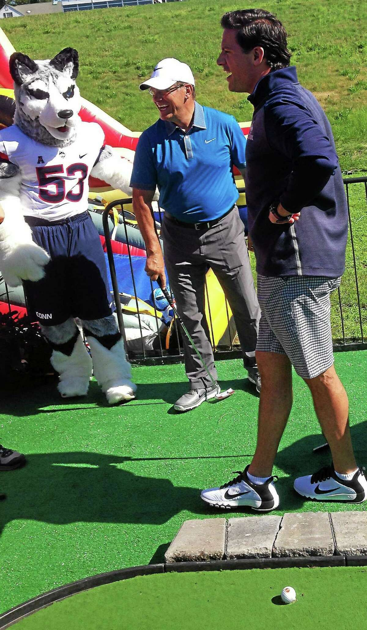 UConn football coach Bob Diaco, right, and women's basketball coach Geno Auriemma participate in the mini-golf tournament on Wednesday.