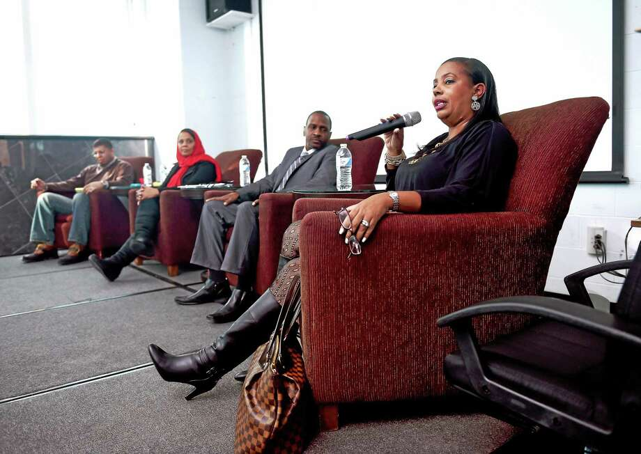 From left, James Hillhouse High School Principal Kermit Carolina, educator Patricia Abdur-Rahman and Hamden High School Principal Gary Highsmith listen to Doris Dumas, president of the Greater New Haven Branch of the NAACP, speak during a panel discussion of Malcolm X at Hillhouse Sunday in New Haven. Photo: Arnold Gold-New Haven Register