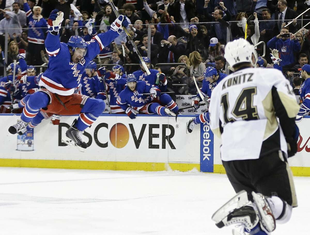 The Rangers' Ryan McDonagh (27) and Pittsburgh Penguins' Chris Kunitz (14) react to the game-winning, overtime goal by the Rangers' Carl Hagelin in Game 5. The Rangers won 2-1 to capture the series 4-1.