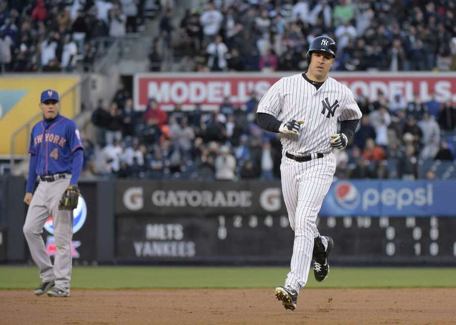 The Yankees' Mark Teixeira rounds the bases after hitting a two-run home run during the first inning as the  Mets' Wilmer Flores, left, looks on. Teixeira hit two homers in the Yankees' 6-1 victory. Photo: Bill Kostroun — The Associated Press   / FR51951 AP