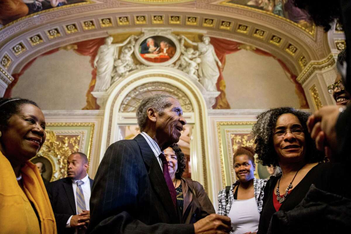 Loretta Lynch's father, Lorenzo Lynch, center, accompanied by Rep. Sheila Jackson Lee, D-Texas, left, greets supporters off the Senate floor on Capitol Hill in Washington Thursday after the Senate voted to confirm Loretta Lynch for Attorney General. Lynch won confirmation to serve as the nation's attorney general, ending months of delay.