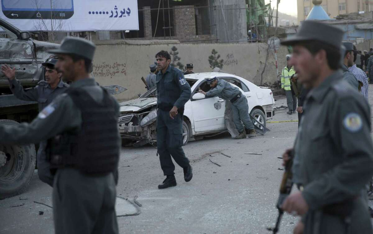 A traffic policeman moves a damaged vehicle at the site of a suicide attack in Kabul, Afghanistan, Wednesday. The suicide car bombing in the heart of the Afghan capital killed several people and wounded tens, according to Afghan security officials.