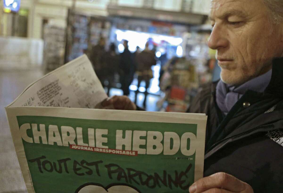 In this Jan. 14, 2015 photo, Jean Paul Bierlein reads the latest issue of Charlie Hebdo outside a newsstand in Nice, southeastern France.