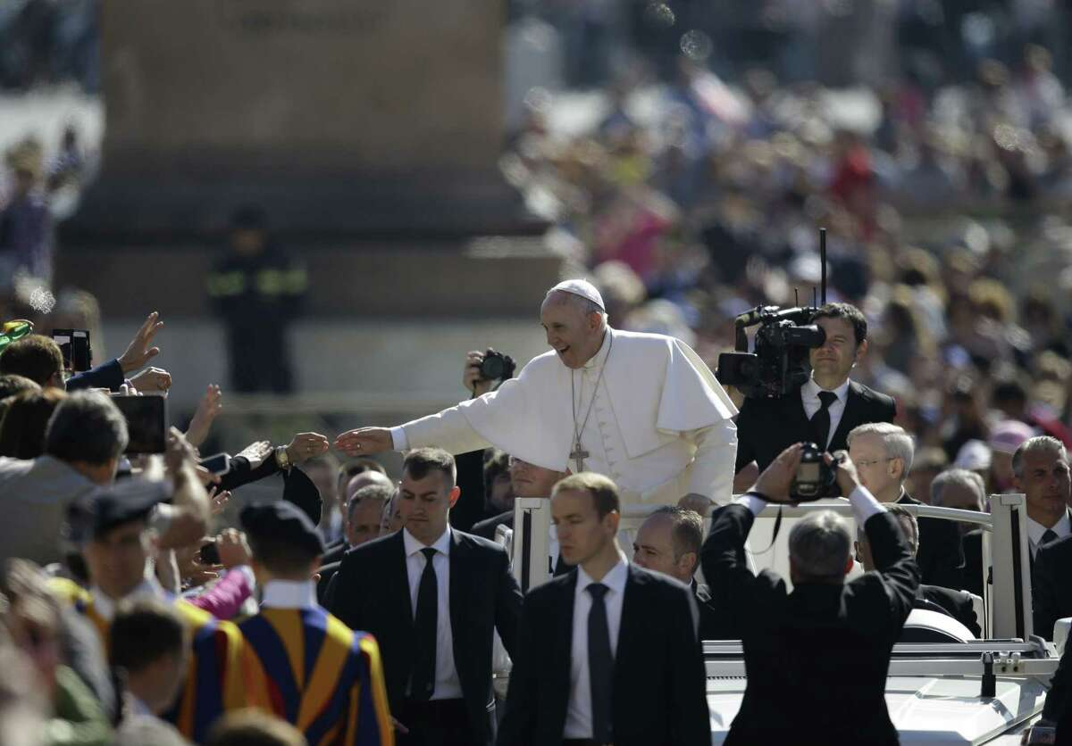 Pope Francis, center, waves to faithful as he arrives for his weekly general audience, in St. Peter's Square, at the Vatican, Wednesday, April 22, 2015. (AP Photo/Gregorio Borgia)