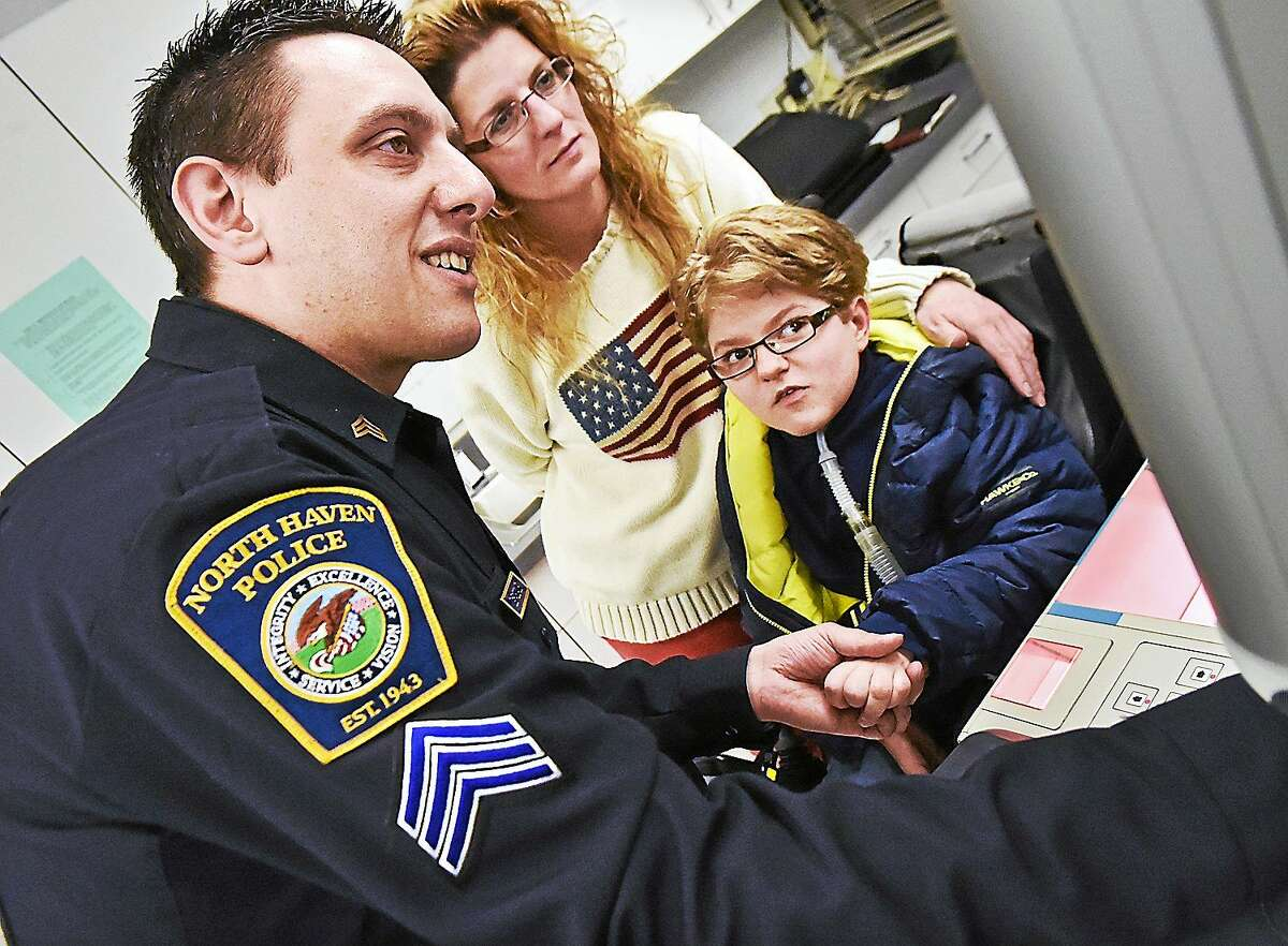 Sgt. Tony DePascale and 9-year-old Hunter Pagueau watch his fingerprint show up on the computer monitor during a short tour at the North Haven Police Department this week as Hunter's mother, Sharon Agli-Pageau, looks on.