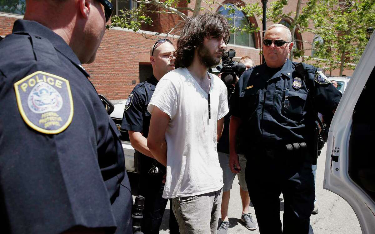 Police detain an unidentified man after removing a cleaver from his car parked in front of the federal court house in Boston, Wednesday, June 24, 2015. Dzhokhar Tsarnaev was in court for formal sentencing for his role in the Boston Marathon bombings. (AP Photo/Michael Dwyer)