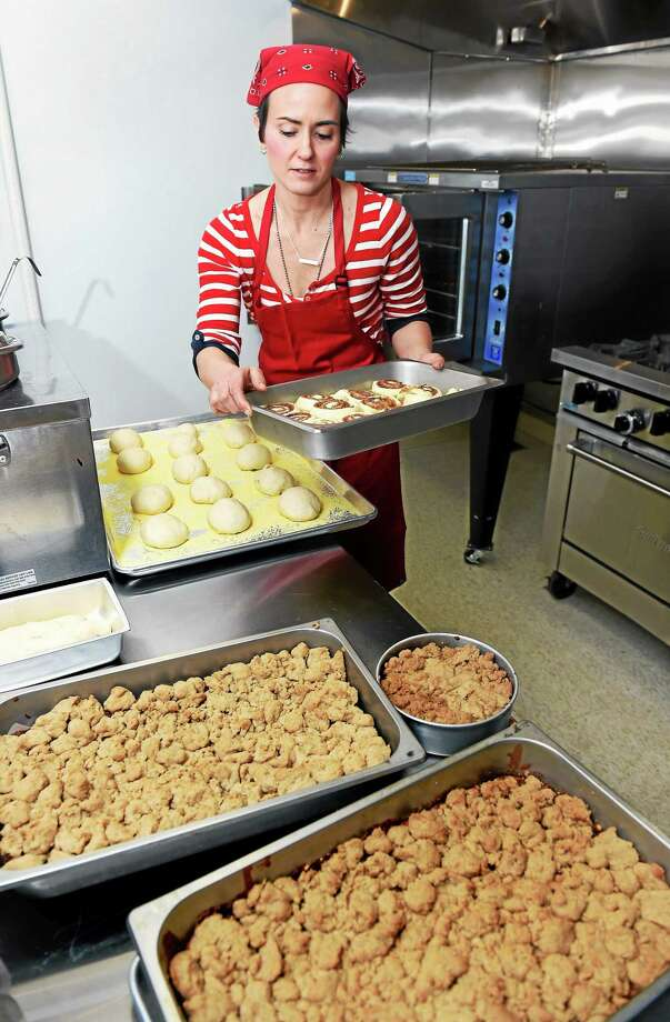 Arnold Gold — New Haven Register    Maggie Flay puts cinnamon buns into the oven at the newly opened Selfish Delights at 400 Boston Post Road in Milford. In the foreground are apple and banana crumb cake. Photo: Journal Register Co.