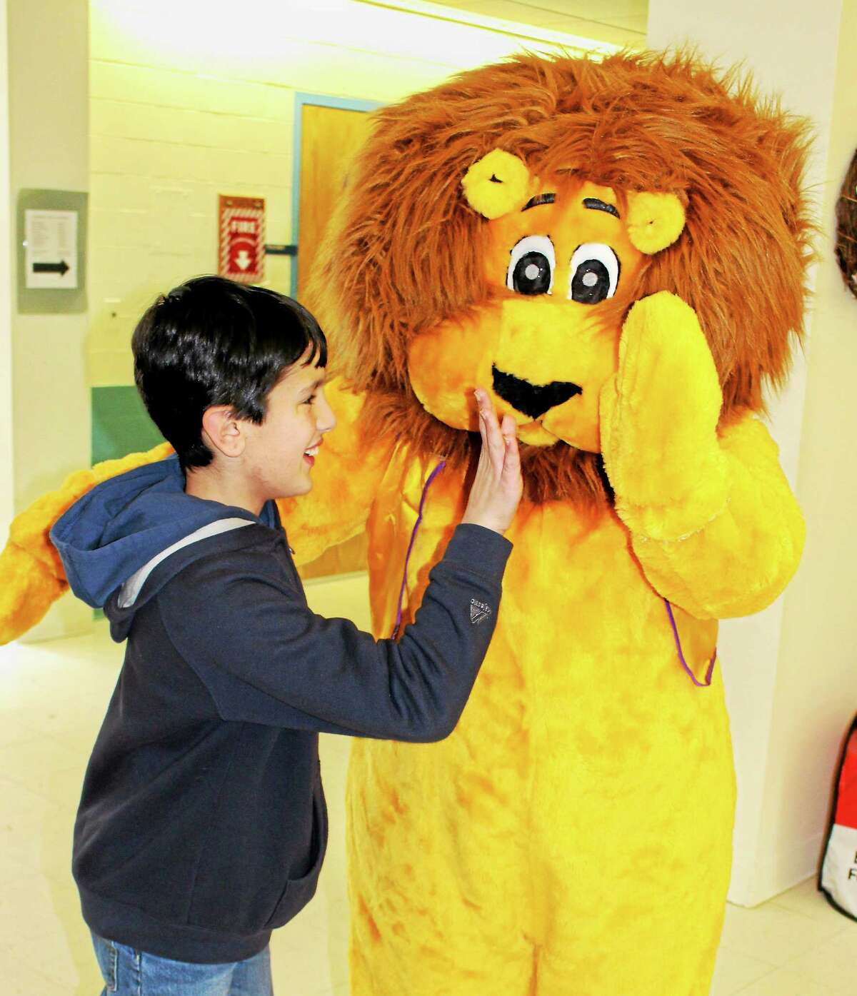 Student Nicholas Criscuolo high-fives Seymour the Lion.