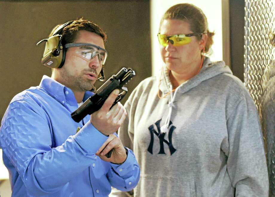 Danny Devlin, co-owner and director of training and instruction at the new Greyson Guns Shooting Club and Range facility on the Boston Post Road in Orange, shares some shooting tips with customer Theresa Colaresi of West Haven. Photo: Peter Hvizdak — New Haven Register   / ©2015 Peter Hvizdak