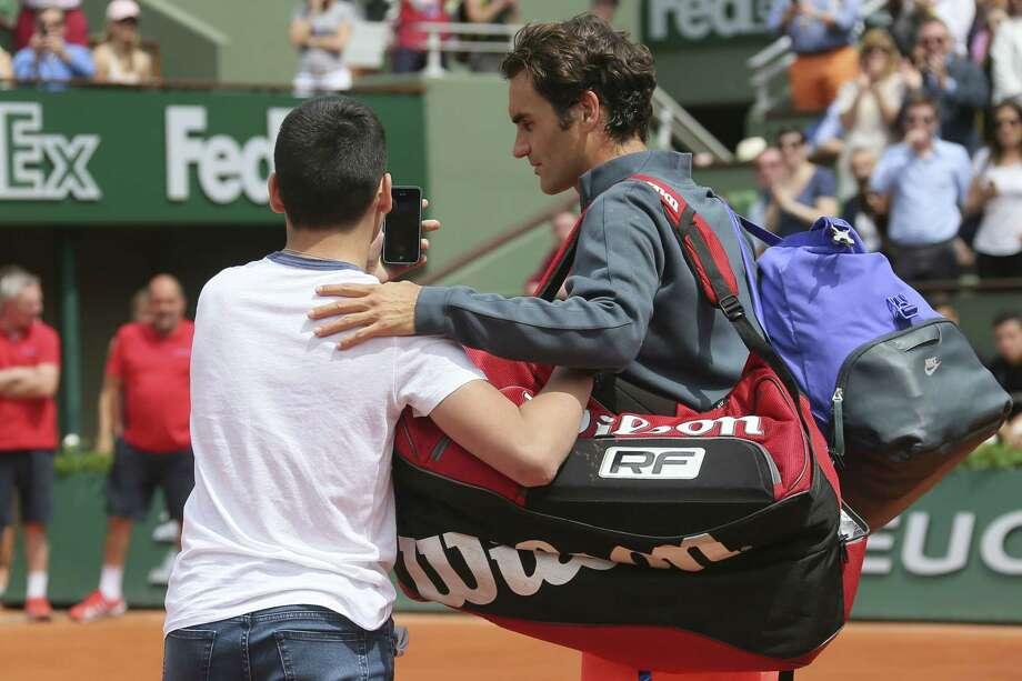 A boy who climbed down from the stands takes a selfie with Switzerland's Roger Federer in the first round match of the French Open on Sunday. Photo: David Vincent — The Associated Press    / AP