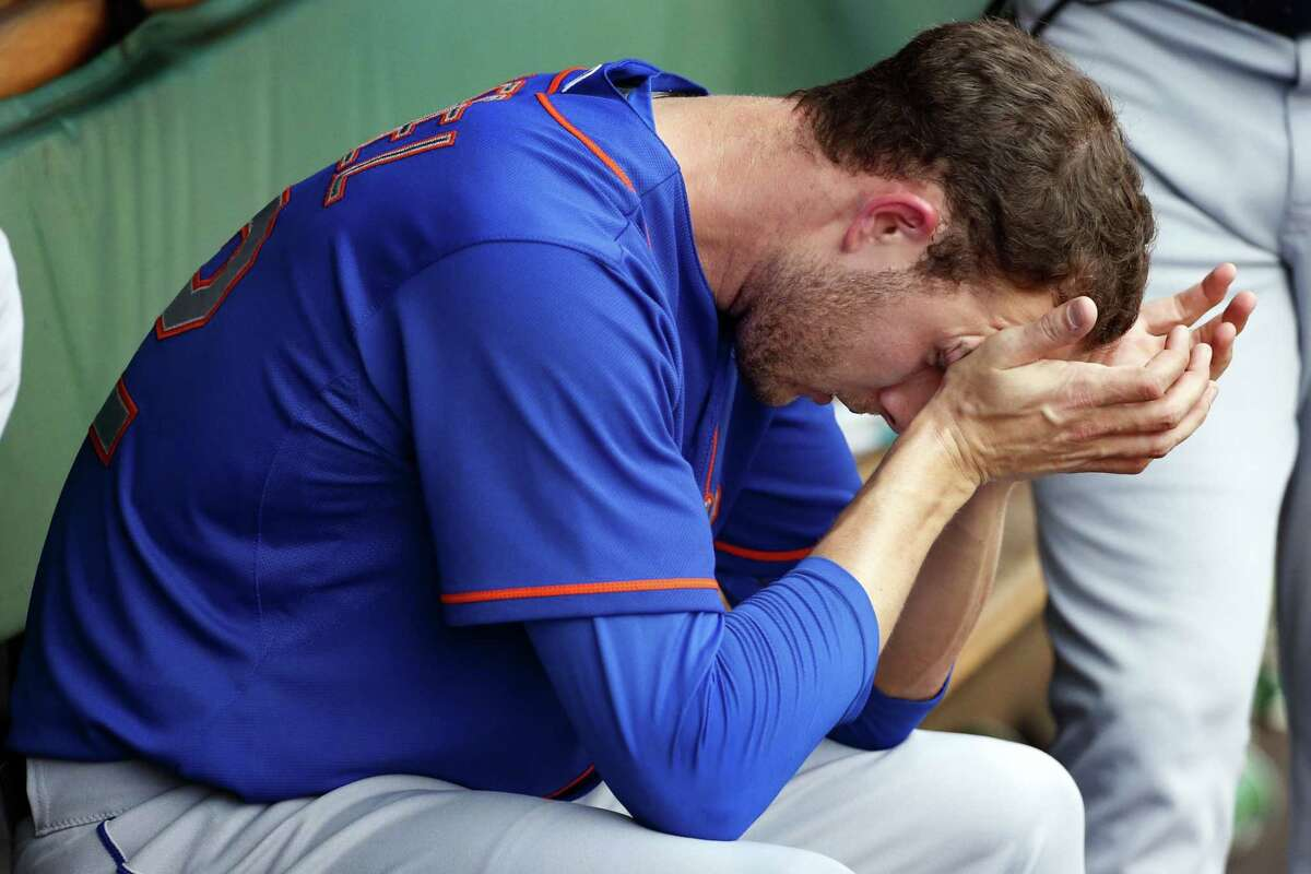 Mets relief pitcher Erik Goeddel sits in the dugout after giving up a three-run home run to Starling Marte in the sixth inning on Sunday.