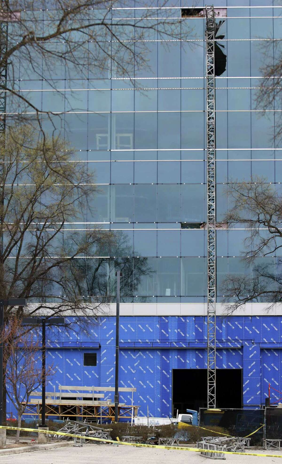 Yellow tape surrounds the piece of scaffolding that fell to the ground as a large section of framework hangs near shattered windows of the Charter Square building at the scene of a construction accident in downtown Raleigh, NC Monday, March 23, 2015. A scaffolding fell and crashed into the Charter Square project, killing three workers and sending another to a hospital. (AP Photo/The News & Observer, Harry Lynch)