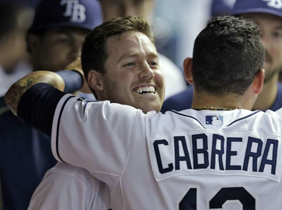 Tampa Bay Rays' Jake Elmore, left, gets a hug from Asdrubal Cabrera in the dugout after Elmore hit a home run off Boston Red Sox relief pitcher Edward Mujica during the seventh inning Wednesday. Photo: The Associated Press   / AP