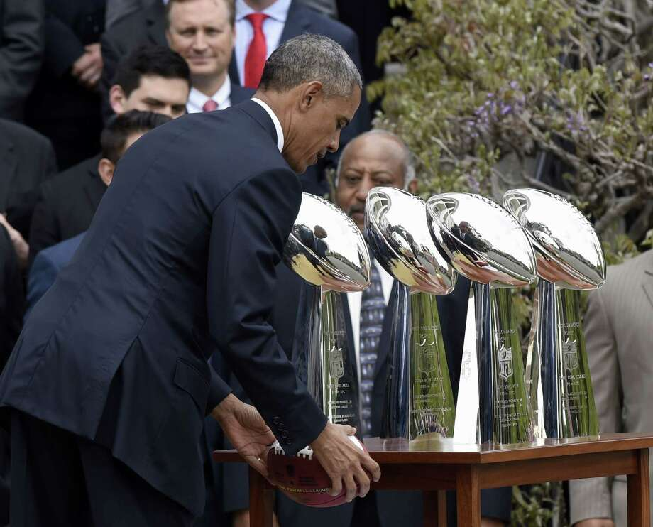 President Barack Obama sets down a football he was given during a Thursday ceremony on the South Lawn of the White House in Washington, where he honored the Super Bowl champion New England Patriots. Photo: Susan Walsh — The Associated Press   / AP
