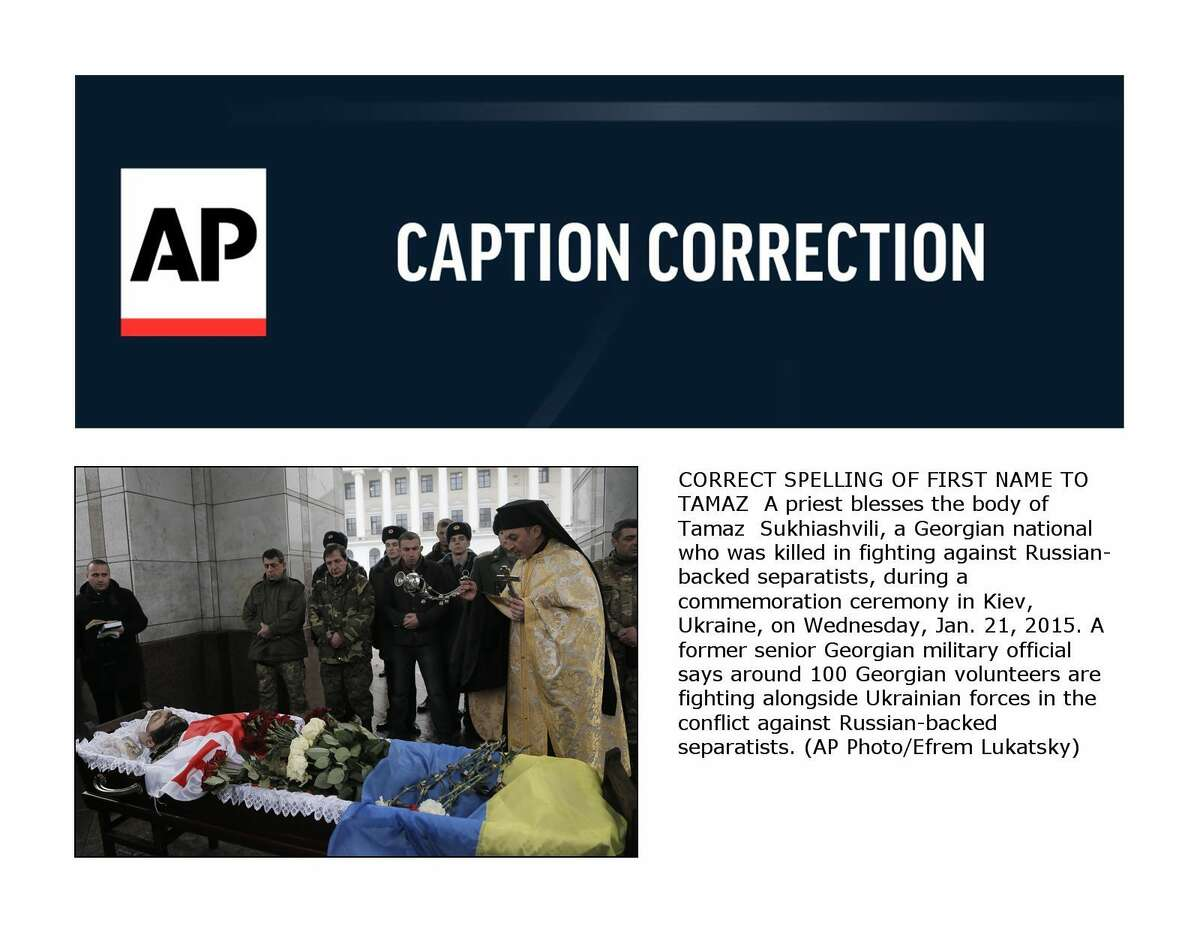 CORRECT SPELLING OF FIRST NAME TO TAMAZ A priest blesses the body of Tamaz Sukhiashvili, a Georgian national who was killed in fighting against Russian-backed separatists, during a commemoration ceremony in Kiev, Ukraine, on Wednesday, Jan. 21, 2015. A former senior Georgian military official says around 100 Georgian volunteers are fighting alongside Ukrainian forces in the conflict against Russian-backed separatists. (AP Photo/Efrem Lukatsky)