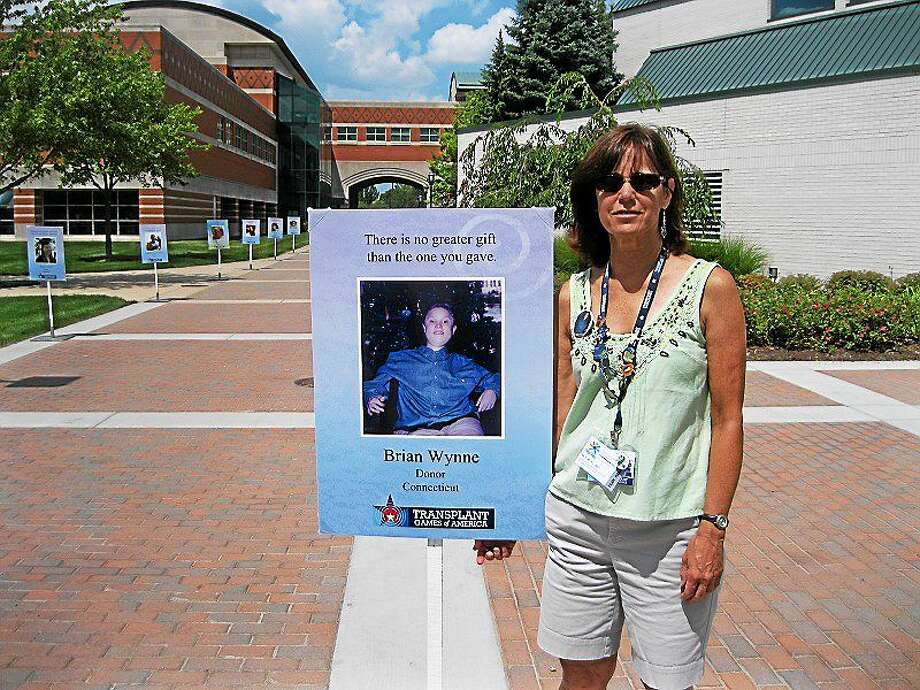 Beth Ballard stands by a poster of her son, Brian Wynne, while attending the Transplant Games in Madison, Wisconsin, a few years ago. Photo: CONTRIBUTED PHOTO