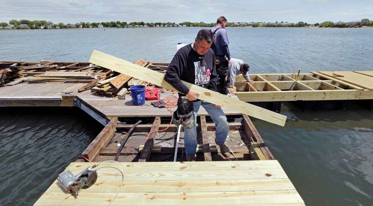 In this May 20, 2015 photo, carpenter Rick Nelson, of Brockton, Mass., installs a new deck plank on a dock heavily damaged during this past winter at the Bay Pointe Marina in Quincy, Mass. The deep freeze that gripped the Northeast this past season dealt a severe blow to marinas and yacht clubs: Ice snapped pilings in half, shredded wooden docks and left behind wreckage that many compare to the effects of a hurricane. Bay Pointe Marina suffered over $1 million in damage from this past winter's storms.
