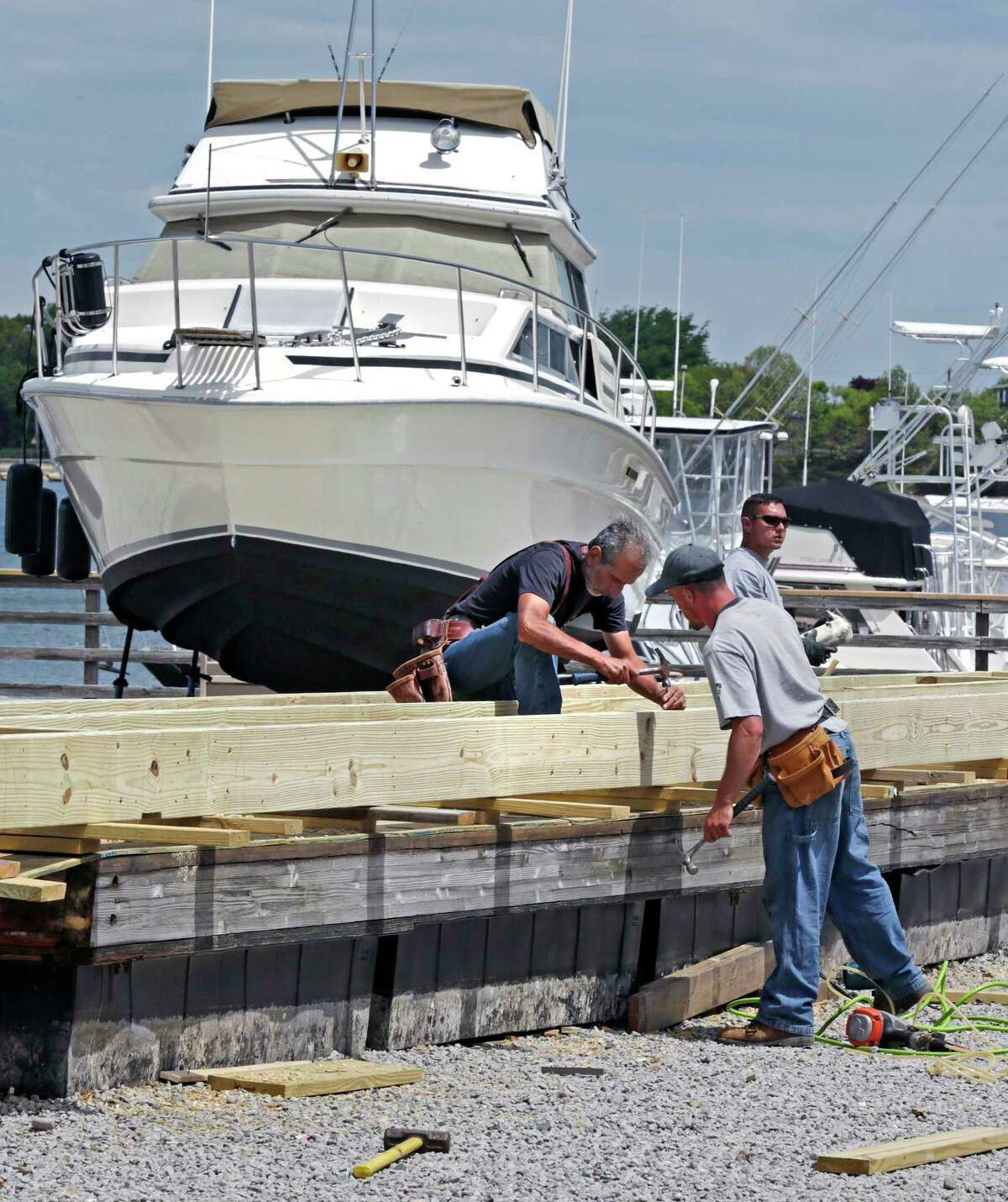 In this May 20, 2015 photo, carpenters install a new deck on a dock heavily damaged during this past winter at the Bay Pointe Marina in Quincy, Mass.