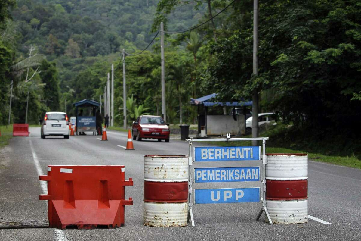"""A check point is seen at the entry point to Malaysia - Thailand border in Wang Kelian, Malaysia on May 24, 2015. Malaysian authorities said Sunday that they have discovered graves in more than a dozen abandoned camps used by human traffickers on the border with Thailand, where Rohingya Muslims fleeing Myanmar have been held. The blue signs read, from top, """"Stop,"""" """"Inspection,"""" and """"UPP (Anti-Smuggling Unit)."""""""