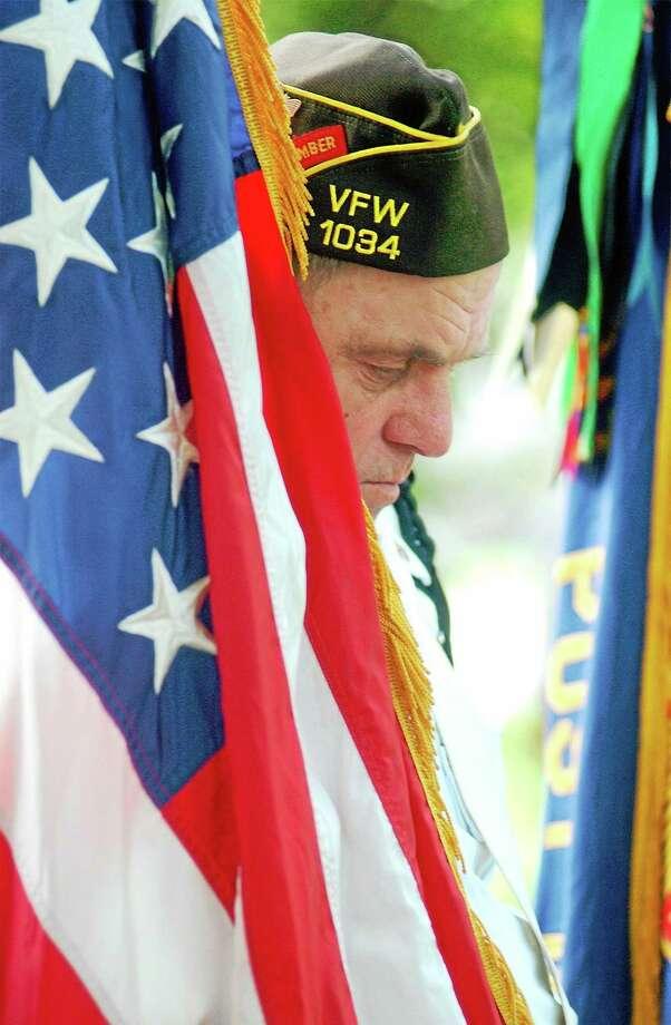 VFW Post 1034 color guard member Richard Barrett holds the flag as he prays during a Memorial Day service held on the Brattleboro town common Monday. (Jason R. Henske/Reformer) Photo: Jason R. Henske — Reformer