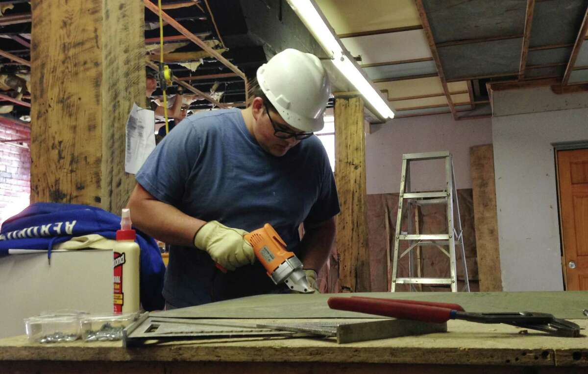 In this March 25, 2015 photo, Nathaniel Blankenship, 19, works to remodel a 1920s-era warehouse into office space in Williamson, W.Va. Blankenship is a crew member in a job program with Coalfield Development Corporation, a nonprofit organization thatís part of a movement to help redevelop vacant or dilapidated buildings in West Virginia. (AP Photo/Jonathan Drew)