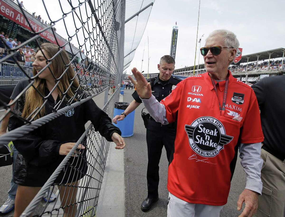 David Letterman waves to fans as he walks through the pit area before the 99th running of the Indianapolis 500 on Sunday.