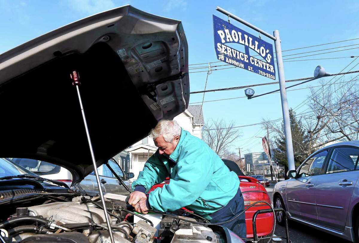Joe Paolillo checks the battery on a car at Paolillo's Service Center on Ashmun St. in New Haven. He has been at this location for 57 years.