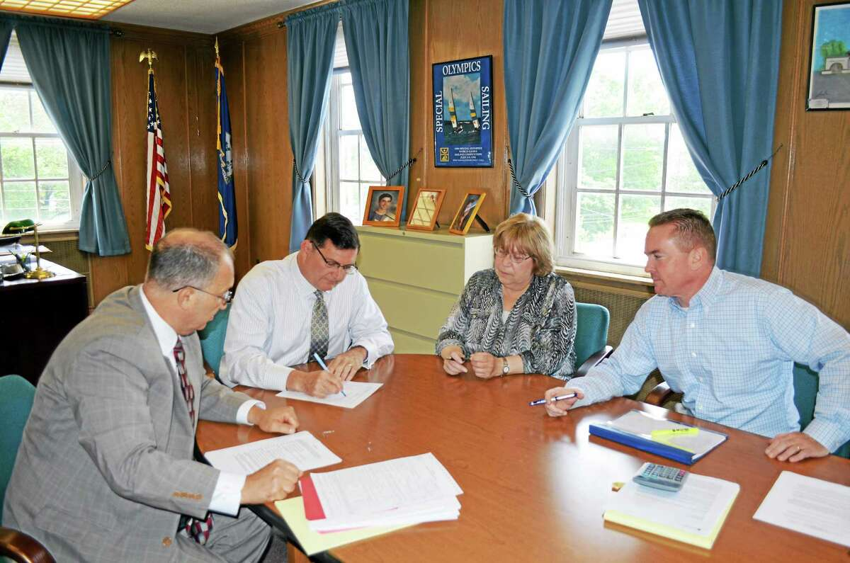 With Corporation Counsel Vin Amendola Jr., left, looking on, Mayor Ed O'Brien signs a limited warranty deed conveying 105 Water St. to The Haven Group LLC Tuesday at City Hall. Witnessing the signing are Chamber of Commerce President Nancy Guman and city Finance Director Kevin McNabola.