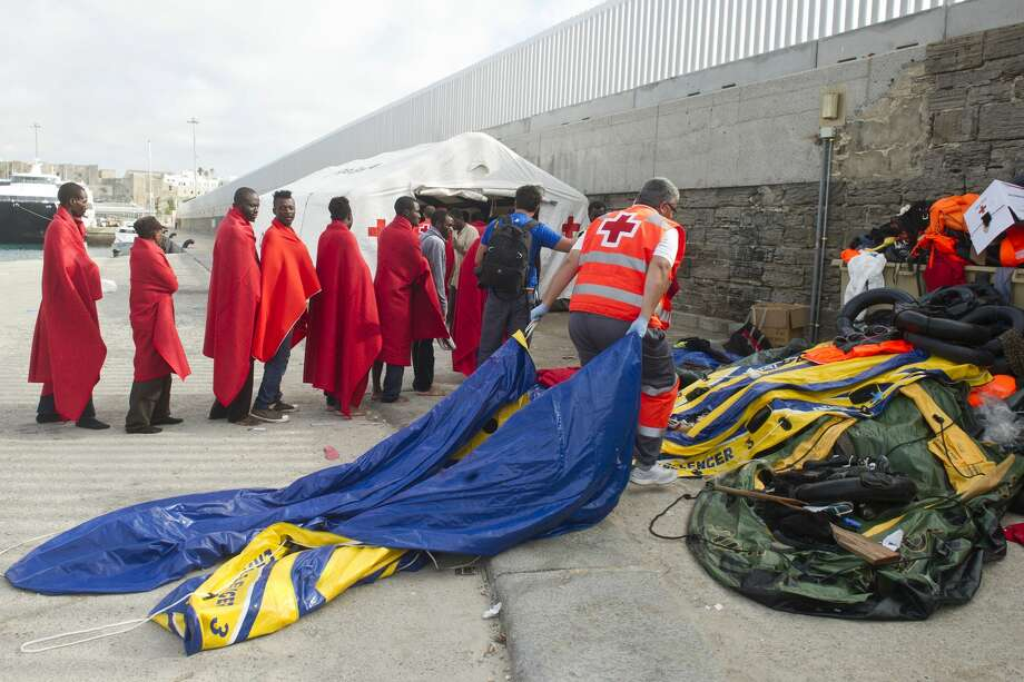 FILE -- In this file photo taken on Aug. 12, 2014, migrants line up as a member of the Spanish Red Cross drags inflatable dinghies they were using in their attempt to reach Spain after they were rescued by the sea rescue service at the Strait of Gibraltar near the coast of Tarifa, southern Spain. The 12-meter (39-foot) rubber dinghies crammed with migrants heading from Libya to Italy arenít supposed to hold more than 20 people. But Mediterranean rescuers find them deflating at sea with more than 100 aboard and believe many sink unnoticed, adding untold victims to the count of 1,700 dead or missing on the journey so far this year. (AP Photo/Marcos Moreno, File) Photo: AP / AP