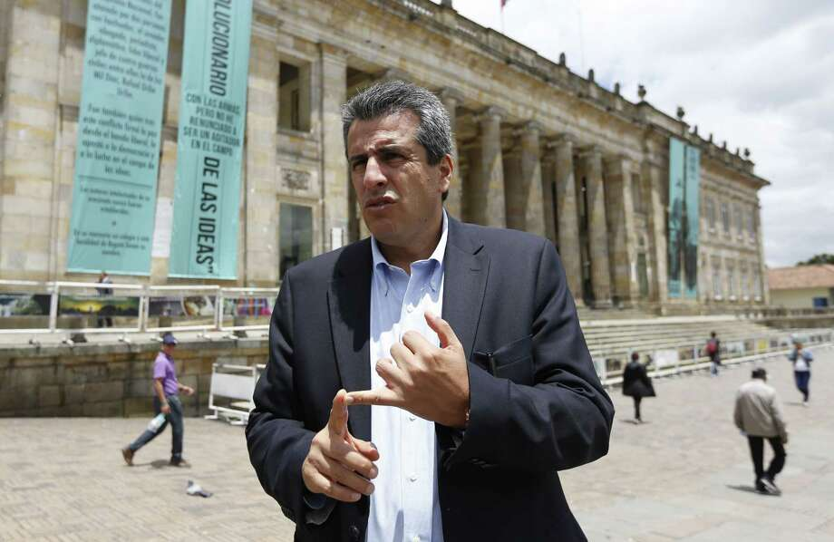 Colombia's Senator Luis Fernando Velasco talks to the press outside Congress in Bogota, Colombia, Thursday, April 23, 2015. Velasco was forced to temporarily abandon his Senate seat and was behind bars when his father suffered a heart attack. After four months in jail, prosecutors determined it was all a set up and his accusers had been paid by his political enemies to testify against him. Velasco was set free, and the lawyer and his accusers were arrested. (AP Photo/Fernando Vergara) Photo: AP / AP