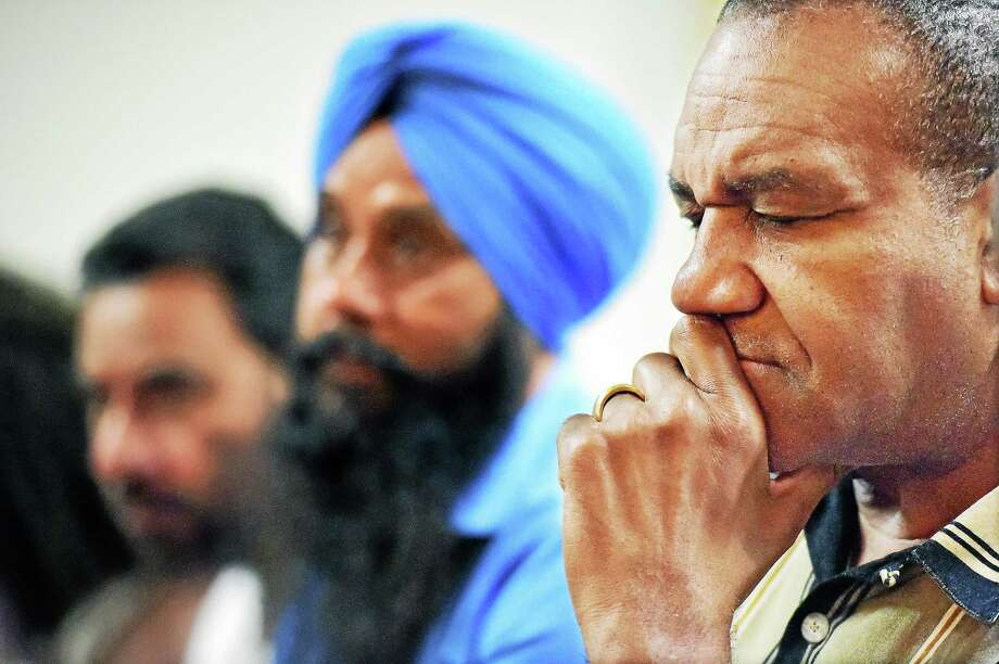 """(Catherine Avalone - New Haven Register)   New Haven residents of all denominations including, Alfred Smith, right, Avtar Singh, center, and Gurjant Singh Narain, left, attend the """"Faith Community Call for Prayer,"""" Tuesday night,  June 23, 2015, at Bethel AME Church praying for the nine individuals killed during a prayer meeting last week, at Mother Emanuel AME Church in Charleston, South Carolina, by suspect Dylann Roof, 21. Photo: Journal Register Co. / New Haven RegisterThe Middletown Press"""
