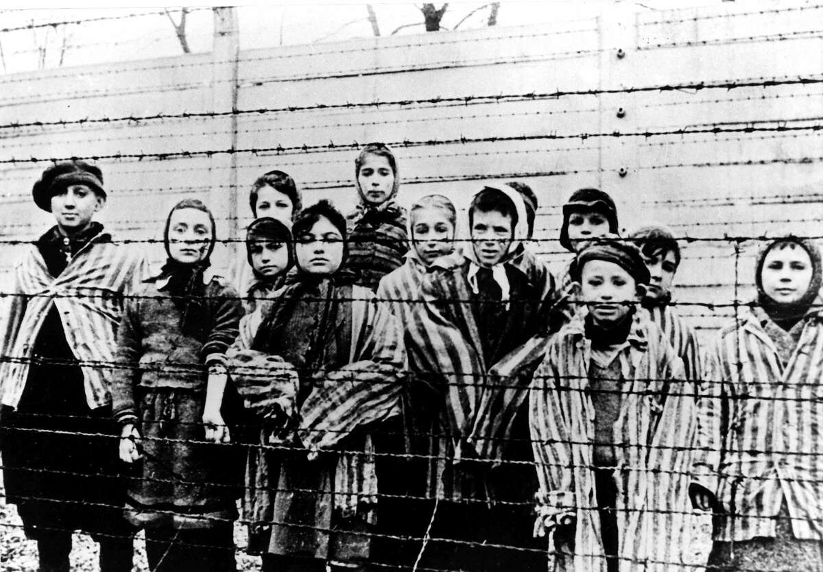 FILE - A picture taken just after the liberation by the Soviet army in January, 1945, shows a group of children wearing concentration camp uniforms behind barbed wire fencing in the Auschwitz Nazi concentration camp. On Thursday Jan. 22, 2015, Russia accused Poland of engaging in a ìmockery of historyî after the Polish foreign minister Grzegorz Schetyna credited Ukrainian soldiers, rather than the Soviet Red Army, with liberating Auschwitz 70-years ago. The latest exchange comes prior to the 70th anniversary of the liberation of Auschwitz by Soviet troops on Jan. 27, 1945, underlining deep tensions between Russia and Poland, which is hugely critical of Russia's recent actions in Ukraine. (AP Photo/FILE)