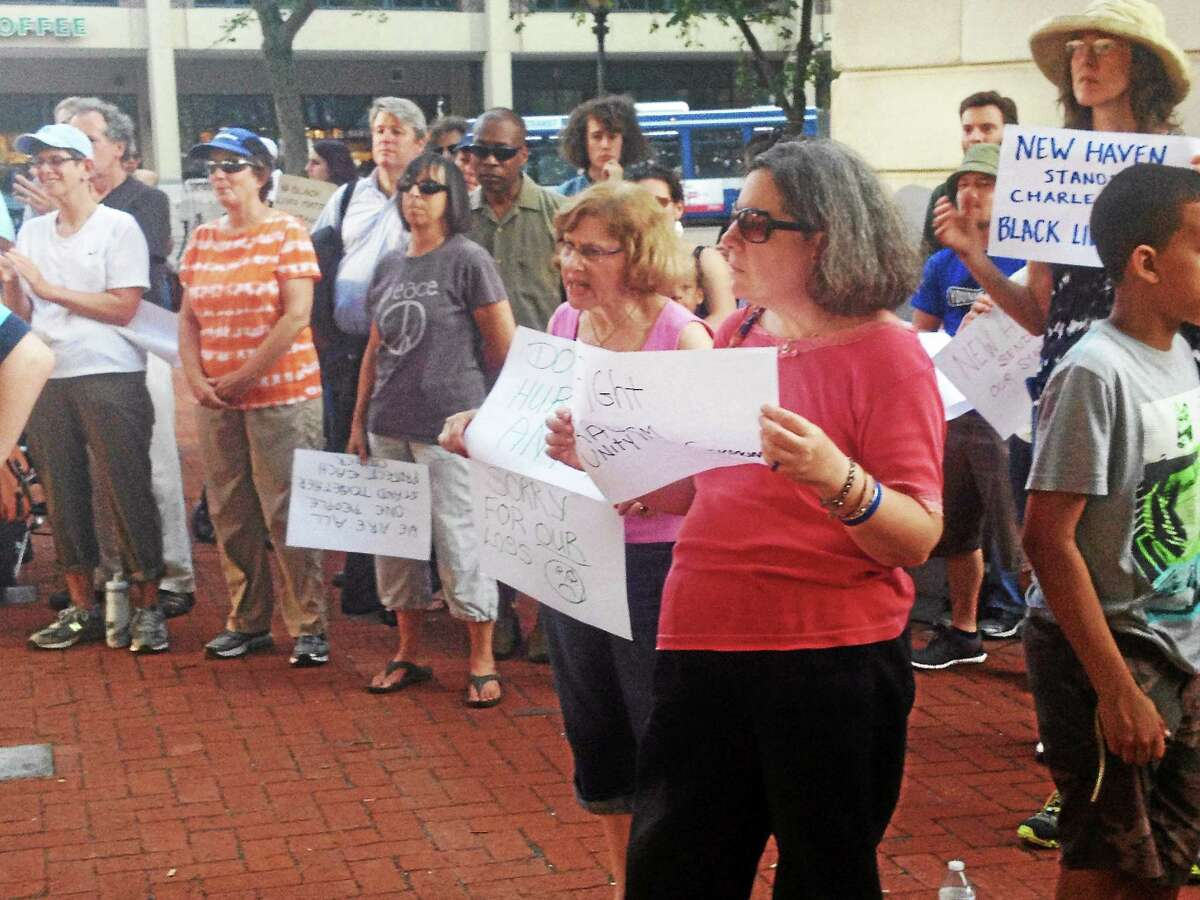 Pam McLoughlin--New Haven Register Part of the crowd on the New Haven Green holds signs against racism at a rally held Sunday, June 22, 2015.