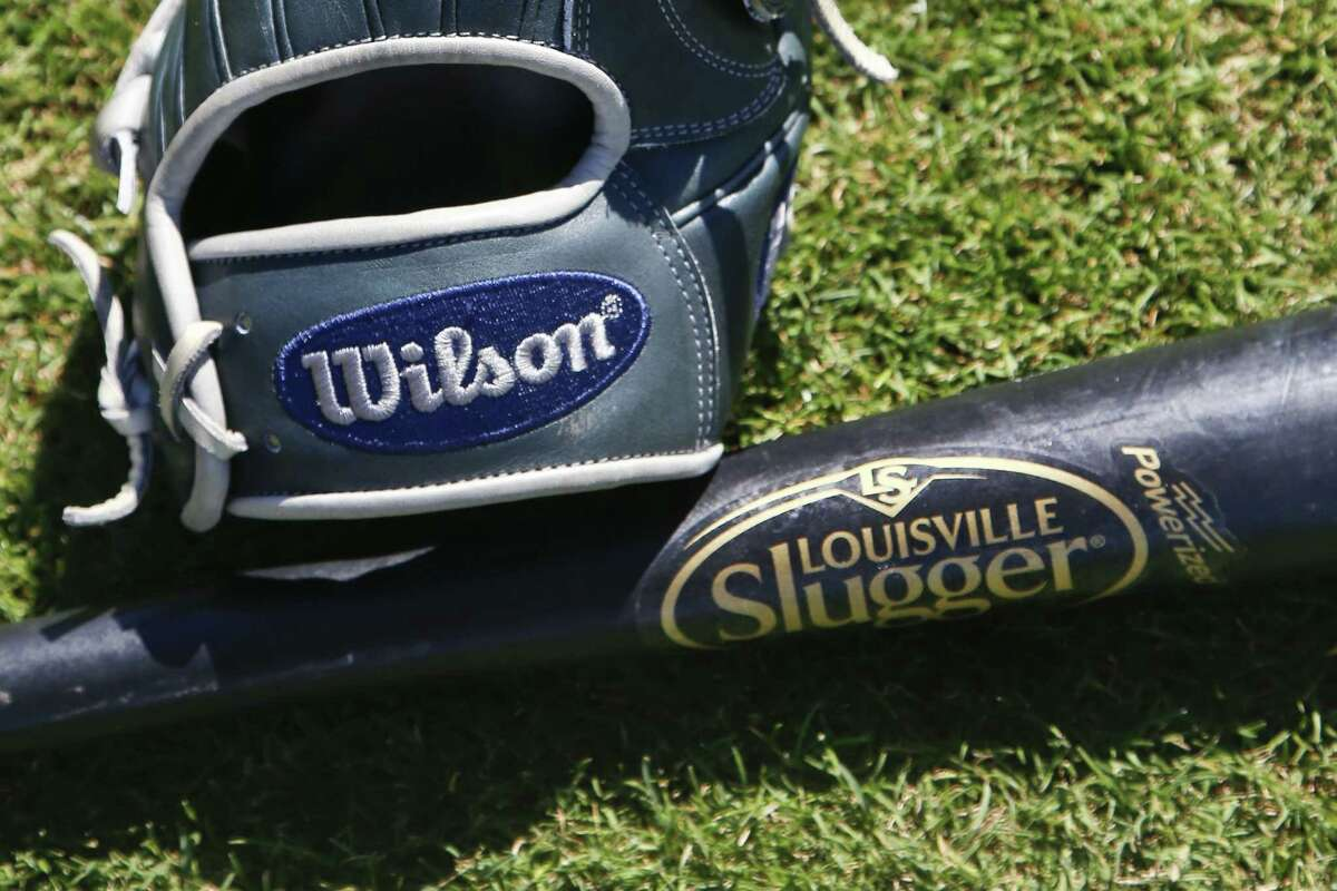 A Wilson A2000 glove and a Louisville slugger bat sit on the field prior to a spring training baseball game between the San Diego Padres and the Chicago White Sox Monday, March 23, 2015, in Peoria, Ariz. Hillerich & Bradsby Co., the company that made bats for a who's who of baseball greats, including Babe Ruth and Ted Williams, announced a deal Monday to sell its Louisville Slugger brand to rival Wilson Sporting Goods Co. for $70 million.