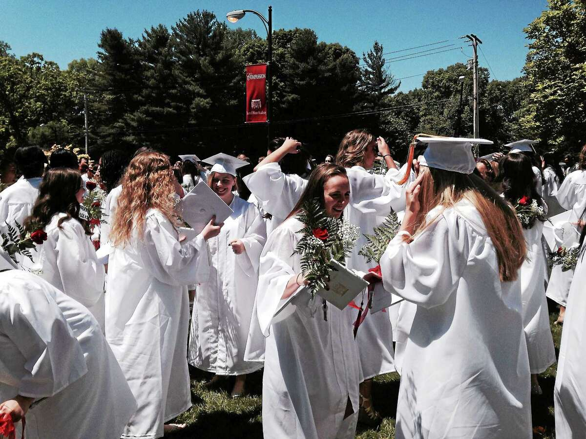 Members of Sacred Heart Academy's Class of 2015 celebrate after receiving their diplomas Saturday, May 23, 2015.
