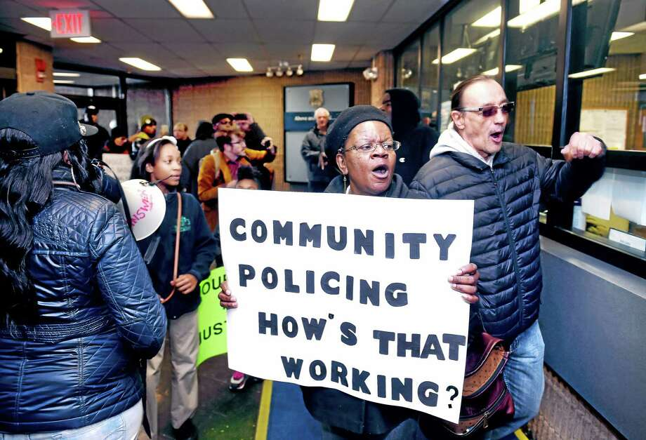 Barbara Fair, center, leads protesters into the lobby of the New Haven Police Department Monday during a protest over injuries a teen is said to have suffered while being arrested. At right is Norman Clement of the Answer Coalition. Photo: Arnold Gold — New Haven Register