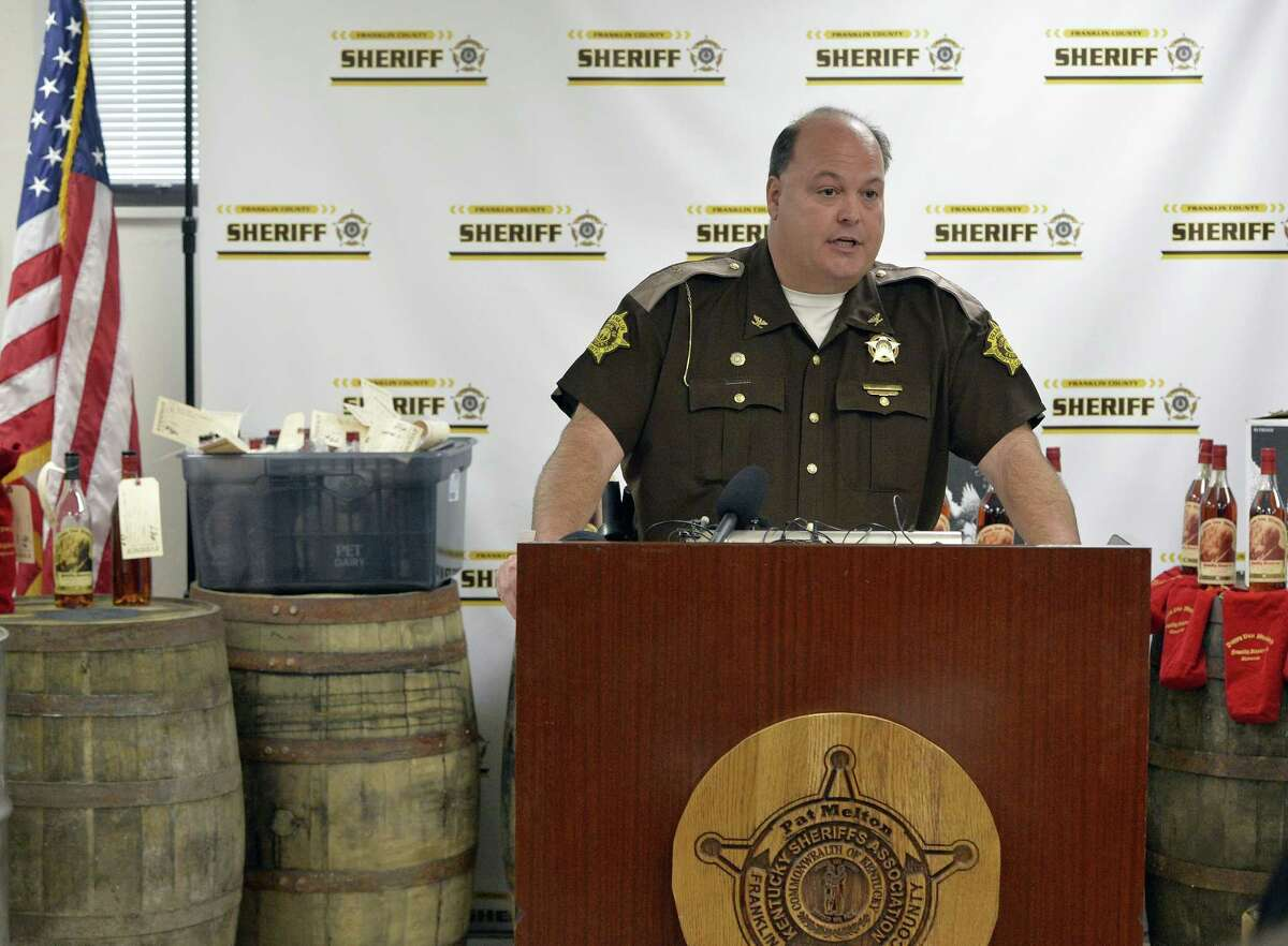 Franklin County Sheriff Pat Melton, standing in front of some of the recovered evidence, responds to a question during a press conference in Frankfort, Ky., April 21, 2015. Nine people were indicted Tuesday relating to the theft of more than $100,000 worth of Wild Turkey and Pappy Van Winkle bourbon, with thefts dating back to 2008. Prosecutors say the scheme led by rogue distillery workers lasted for years and involved tens of thousands of dollars' worth of whiskey. (AP Photo/Timothy D. Easley)