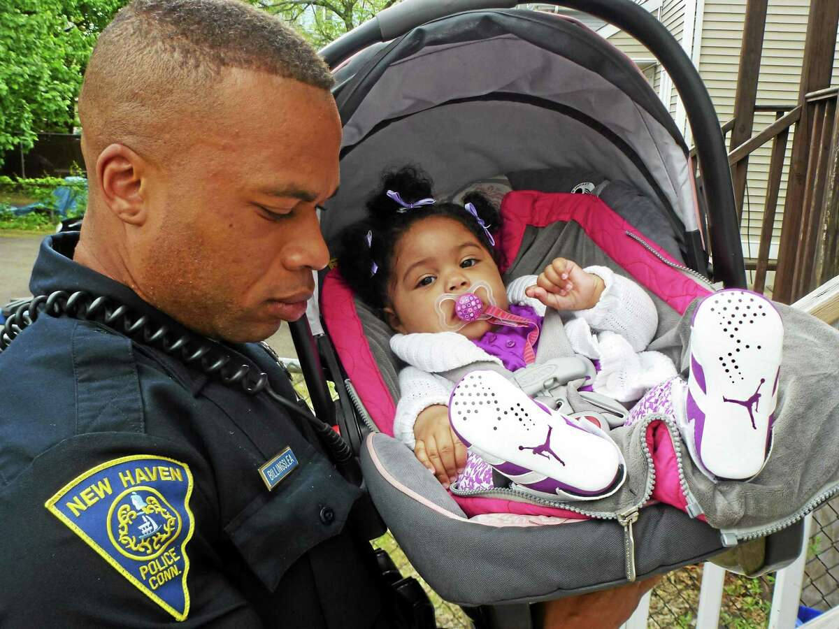 Officer Lesley Billingslea with baby Rylee, who he helped carry in the house while Officer Cherelle Carr helped with Rylee grandmother's groceries.