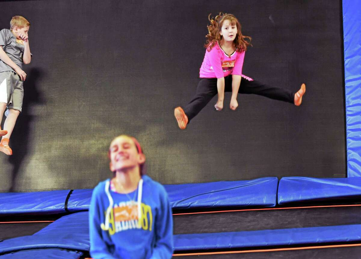 (Peter Hvizdak - New Haven Register) Catherine Norton, 8, of Cheshire, right, flies high at the Sky Zone in Wallingford, Conn., an indoor trampoline park. Sky Zone offers