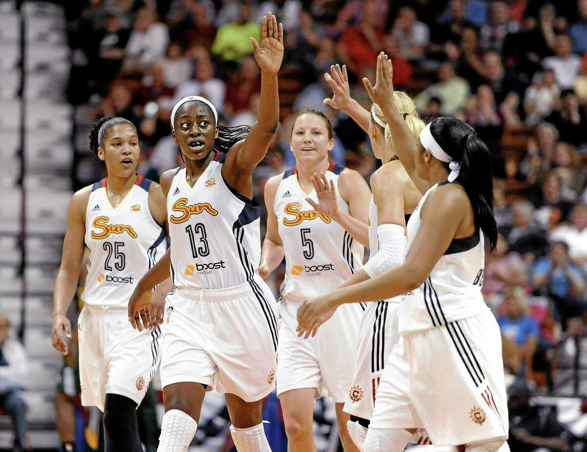 The Connecticut Sun's Chiney Ogwumike (13) reaches to her teammates for a high-five during a May 23, 2014 game against the Seattle Storm in Uncasville.