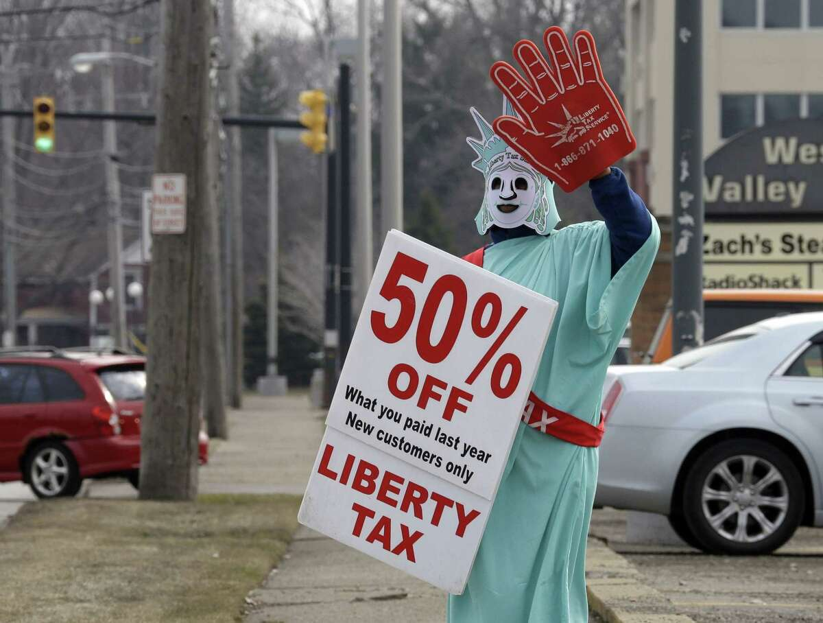 In this March 21, 2015 photo, Brittney Freison, dressed as Lady Liberty, waves to motorists near the Liberty Tax Service office in Berea, Ohio. Wary of rising fees, federal regulators are eyeing ways they can assert tighter oversight upon paid tax preparers who cater to an expanding market of cash-strapped families anxious for their tax refunds.